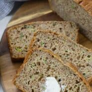 """Overhead view of sliced zucchini bread, with a dab of butter on it. A text overlay reads """"whole wheat zucchini bread."""""""