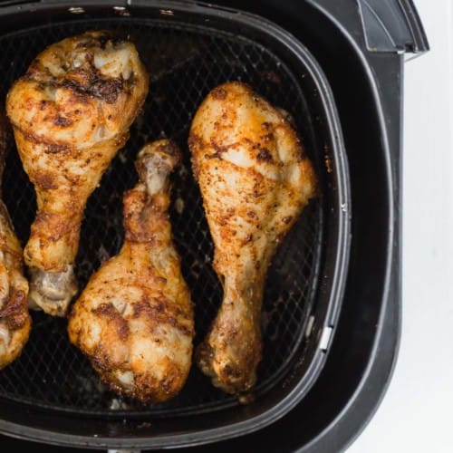 Overhead view of a black air fryer basket with cooked chicken drumsticks inside it.
