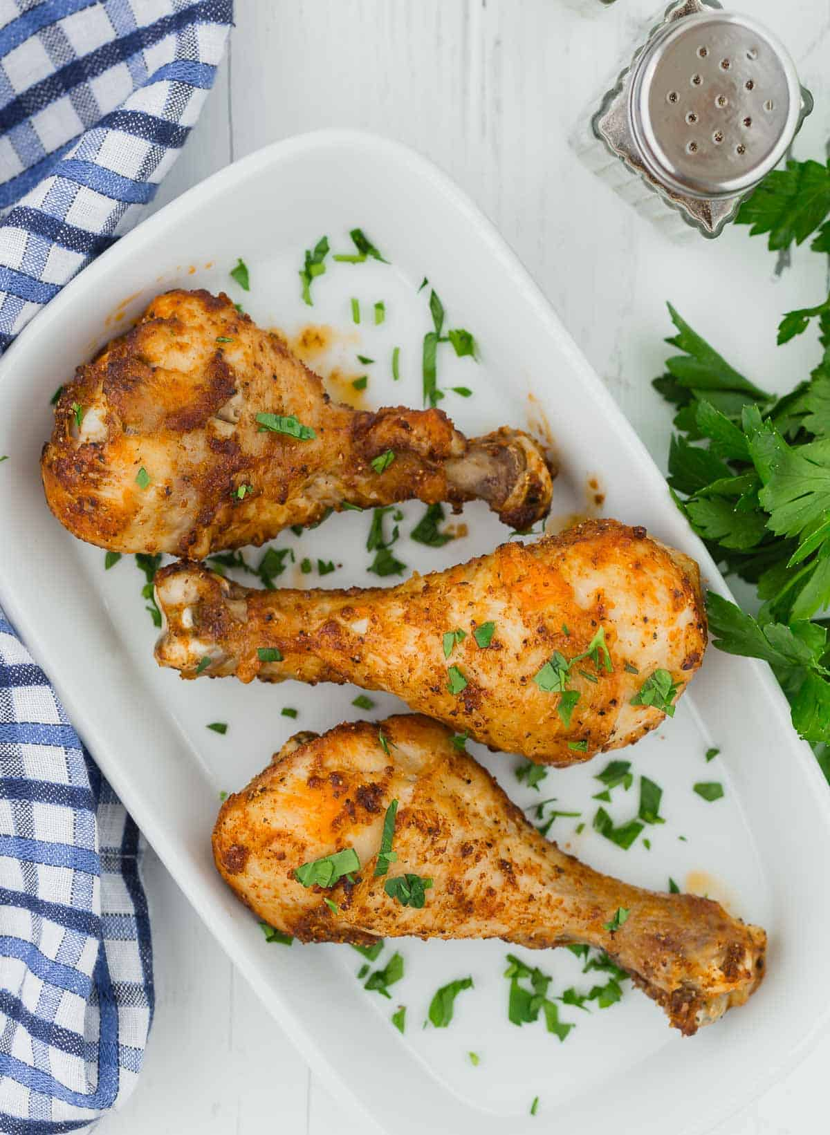 Overhead view of three seasoned chicken drumsticks on a white platter.