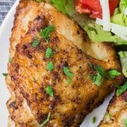 """Two chicken thighs on a plate with salad, text overlay reads """"air fryer chicken thighs, www.rachelcooks.com"""""""