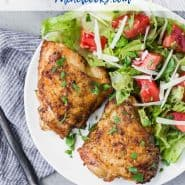 """Two chicken thighs on a plate with salad, text overlay reads """"the best air fryer chicken thighs, www.rachelcooks.com"""""""