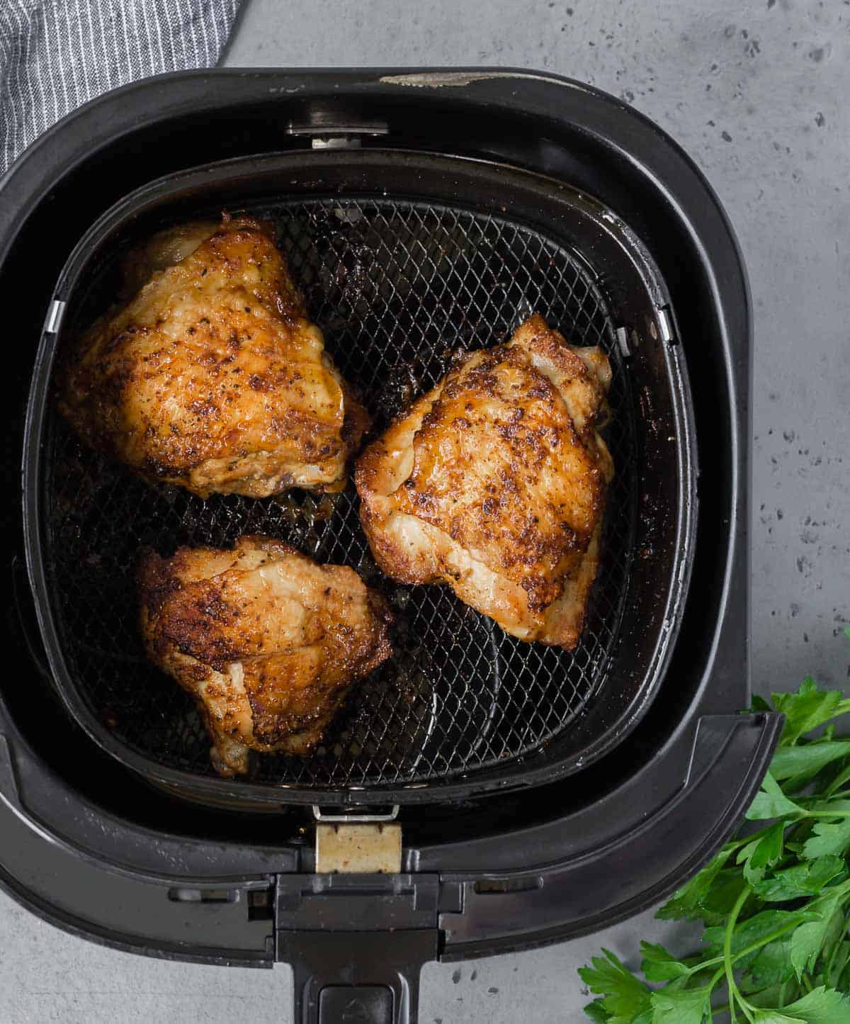 Overhead view of three chicken thighs in an air fryer basket.