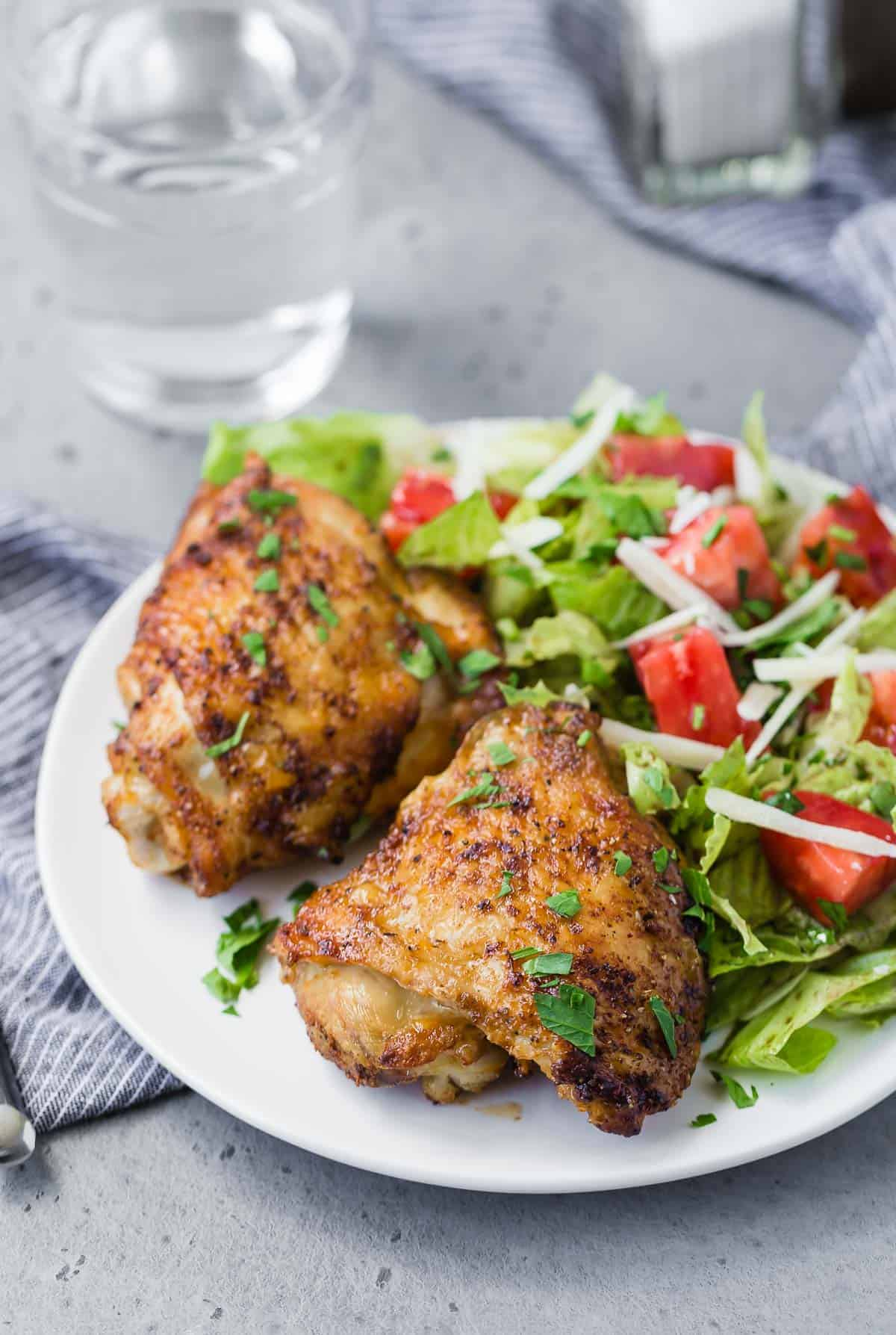 Two chicken thighs on a plate with a tossed salad.
