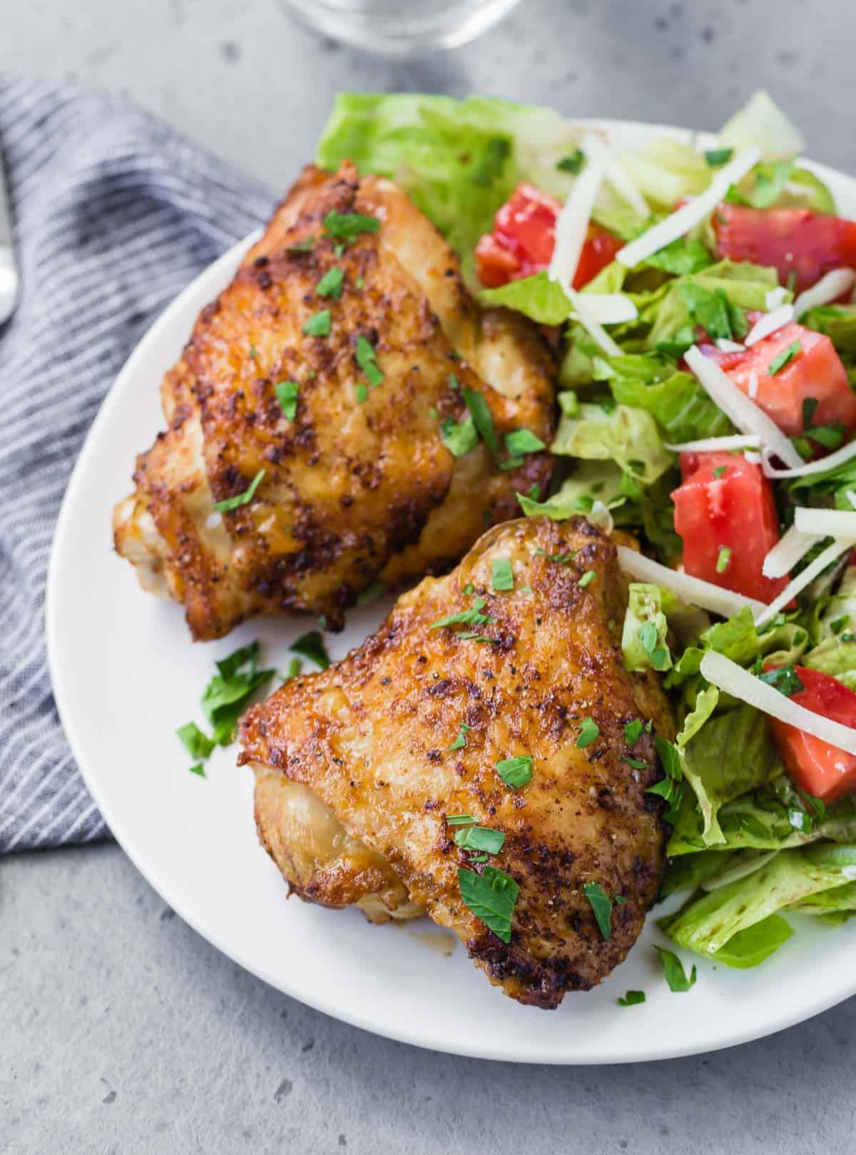 Overhead view of two chicken thighs on a plate with a tossed salad.