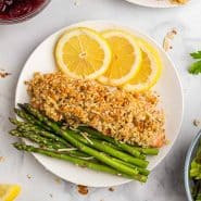 Overhead view of almond and parmesan crusted salmon on a plate with lemon slices and asparaugs.
