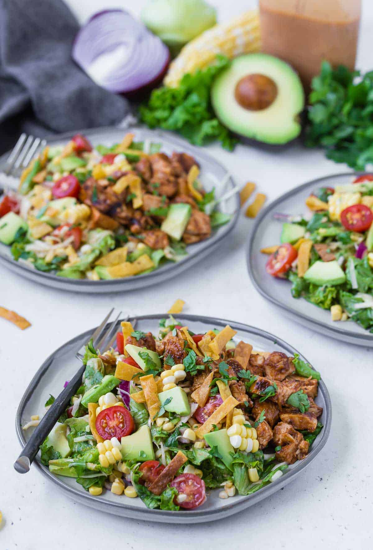 Three plates of a colorful chopped salad on a grey plates. Salad includes bbq grilled chicken, lettuce, onion, tomato, crispy tortilla strips, avocado, corn and more!