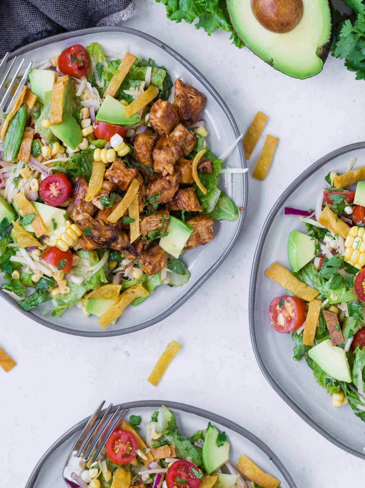 Overhead view of three plates of a colorful chopped salad on a grey plate. Salad includes bbq grilled chicken, lettuce, onion, tomato, crispy tortilla strips, avocado, corn and more!