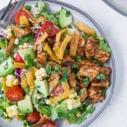 Overhead view of a colorful chopped salad on a grey plate. Salad includes bbq grilled chicken, lettuce, onion, tomato, crispy tortilla strips, avocado, corn and more!