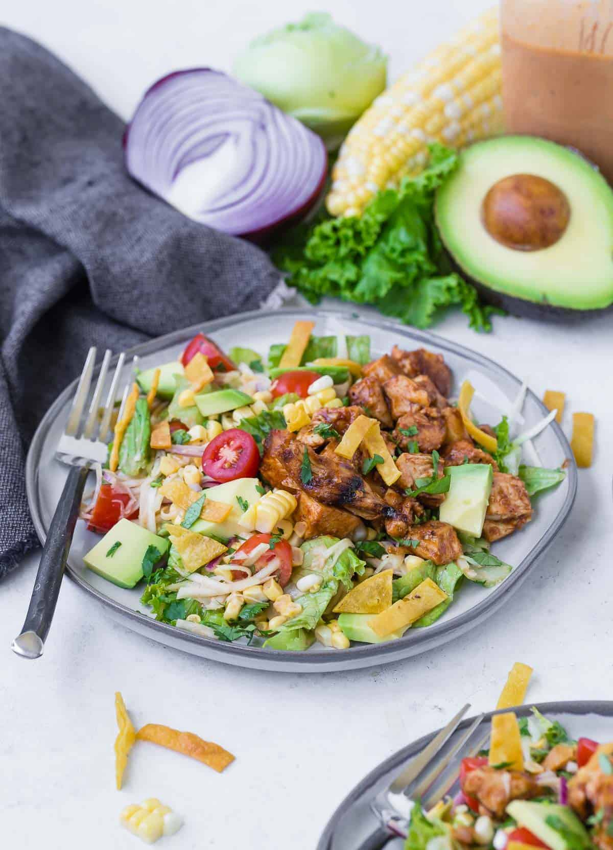 Colorful chopped salad on a grey plate. Salad includes bbq grilled chicken, lettuce, onion, tomato, crispy tortilla strips, avocado, corn and more! Whole ingredients are featured in the background of the image.