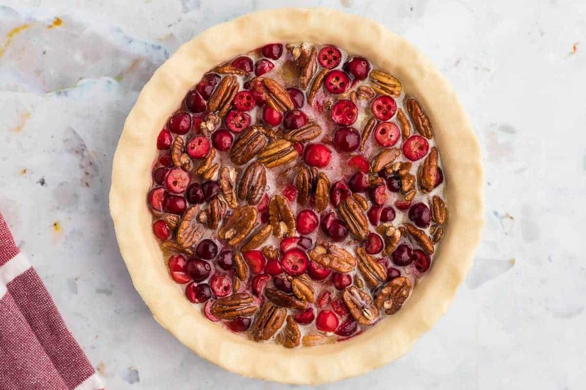 Unbaked pecan pie with cranberries, overhead view.