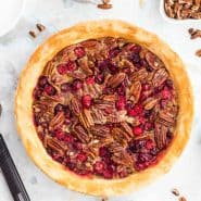 Overhead view of pecan pie with cranberries, surrounded by individual ingredients.