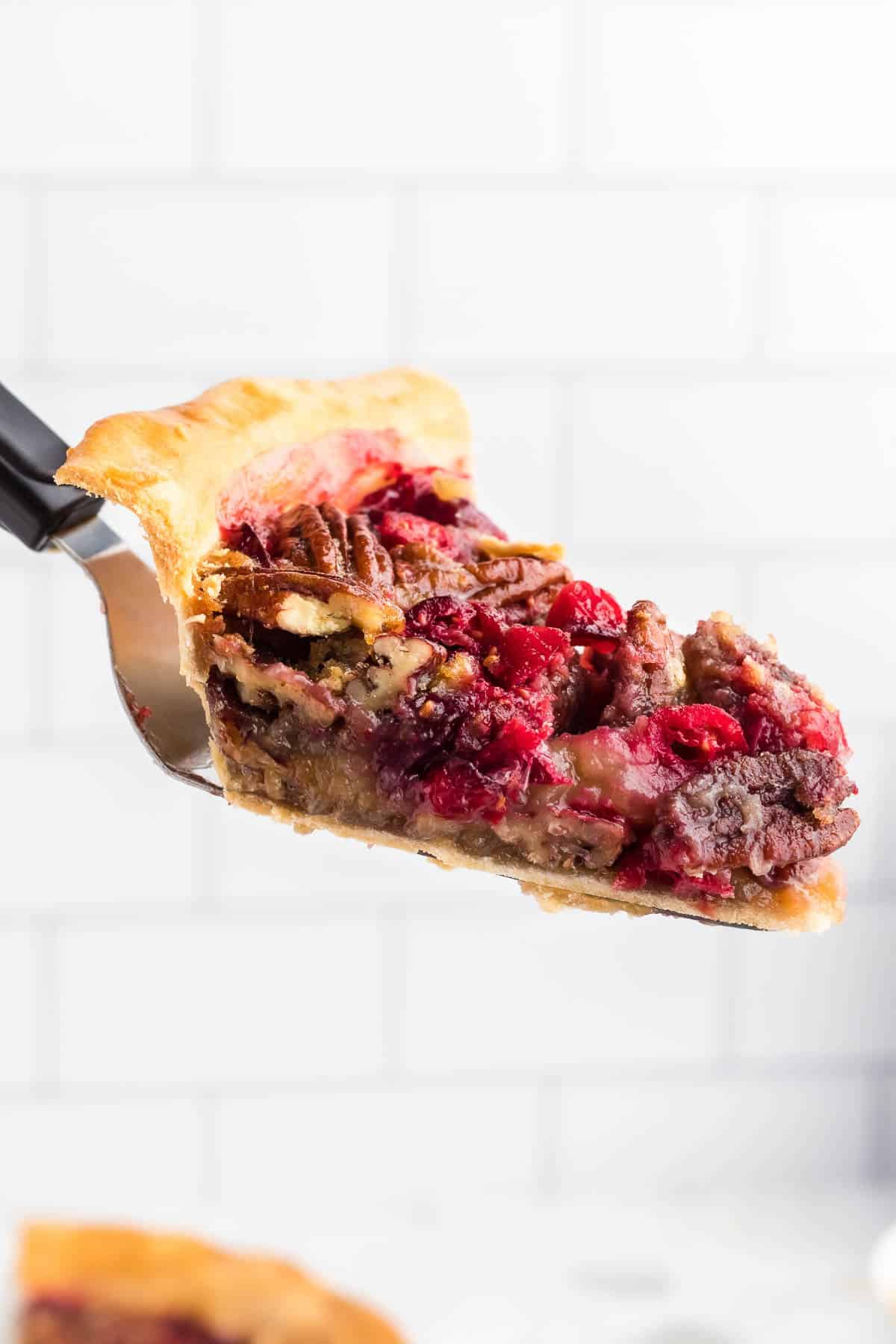Slice of pie with pecans and cranberries on a spatula.