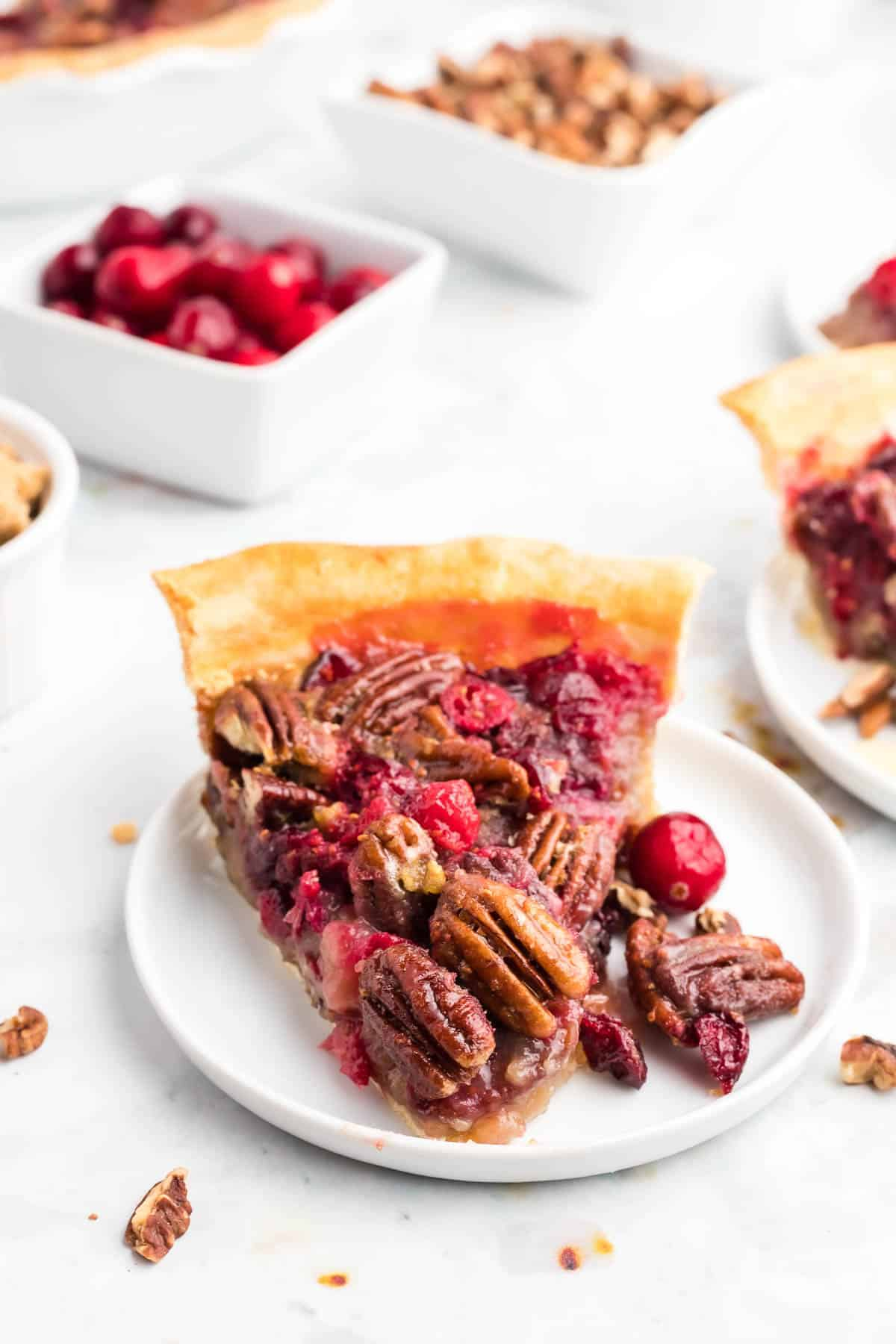 Pie slice on a white plate with cranberries and pecans scattered around.