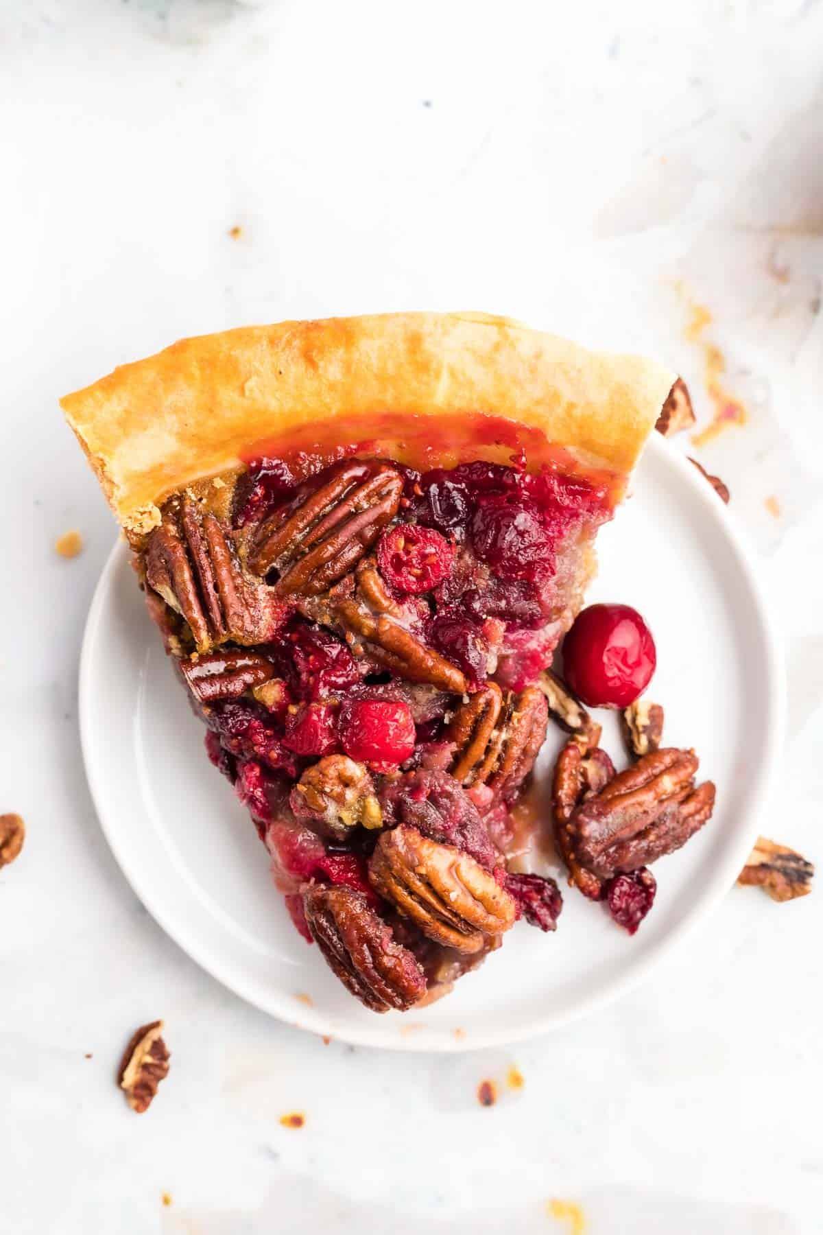 Overhead view of cranberry and pecan pie on a white plate.