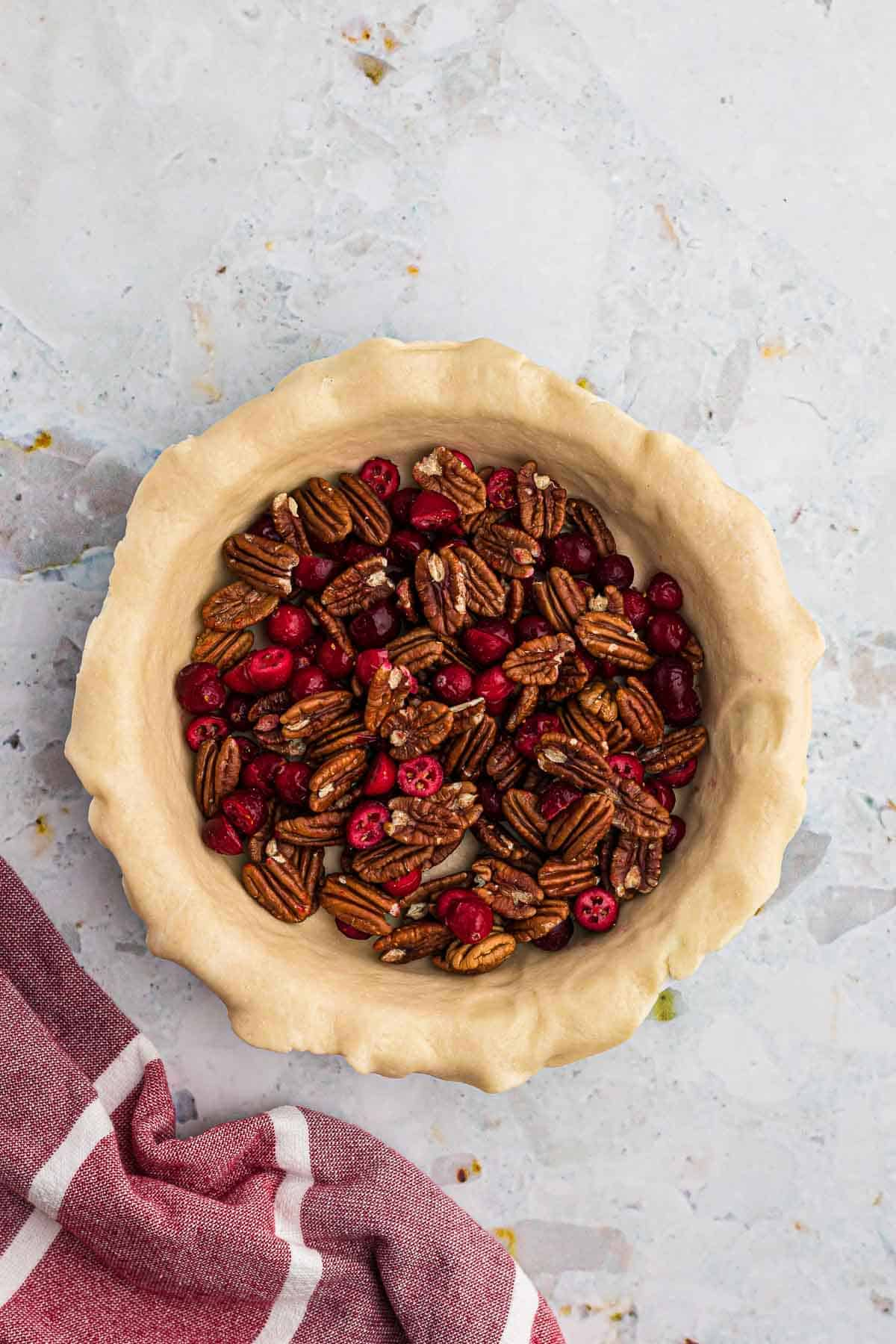 Pecans and cranberries in an unbaked pie crust.