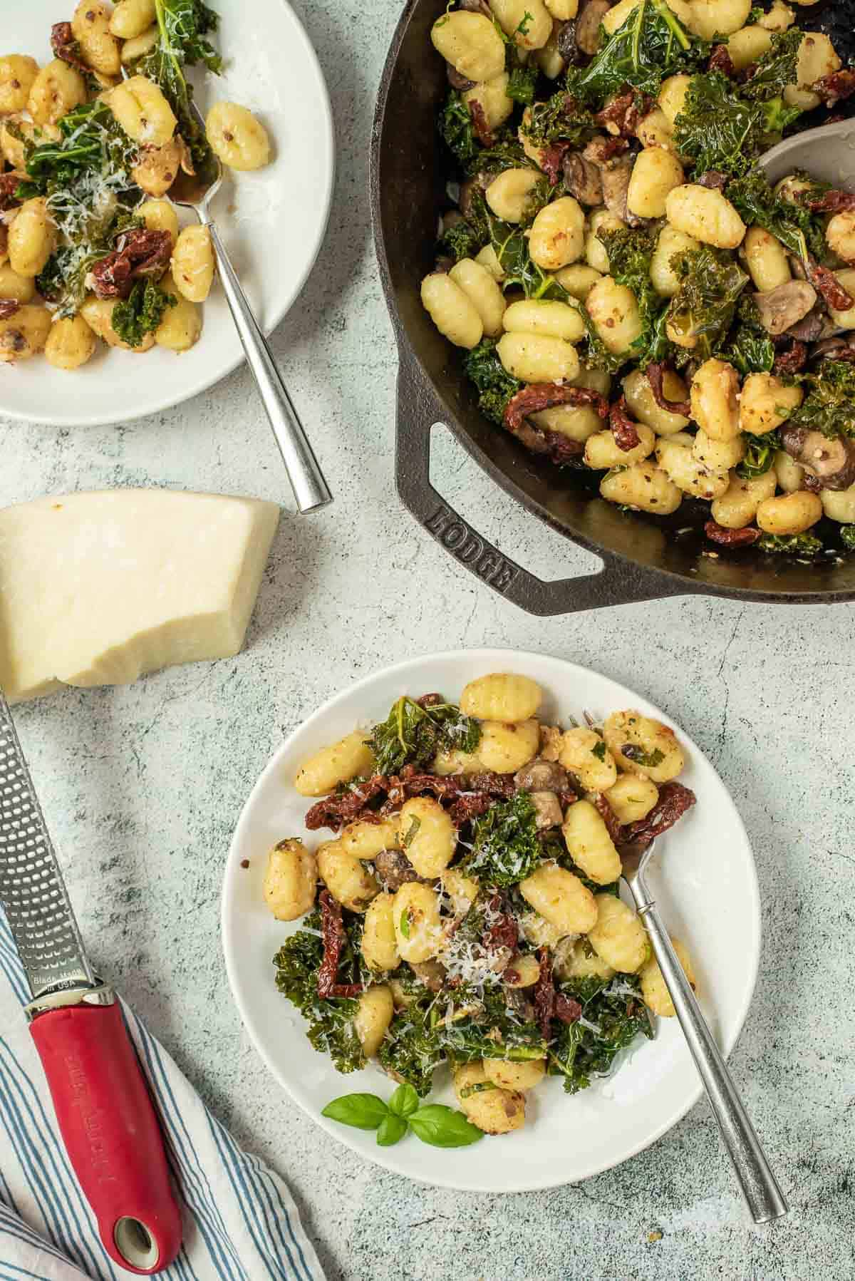 Overhead view of gnocchi with sun-dried tomatoes, kale, and mushrooms.