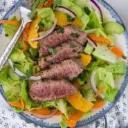 "Steak salad with oranges with a text overlay reading ""steak salad with orange honey dressing"""