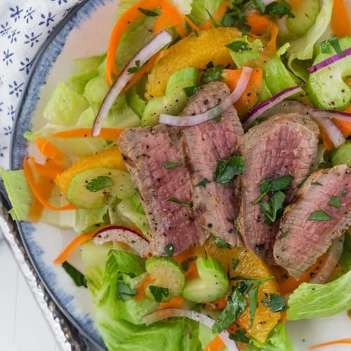 Overhead view of a green leaf lettuce salad topped with steak, oranges, and onion.