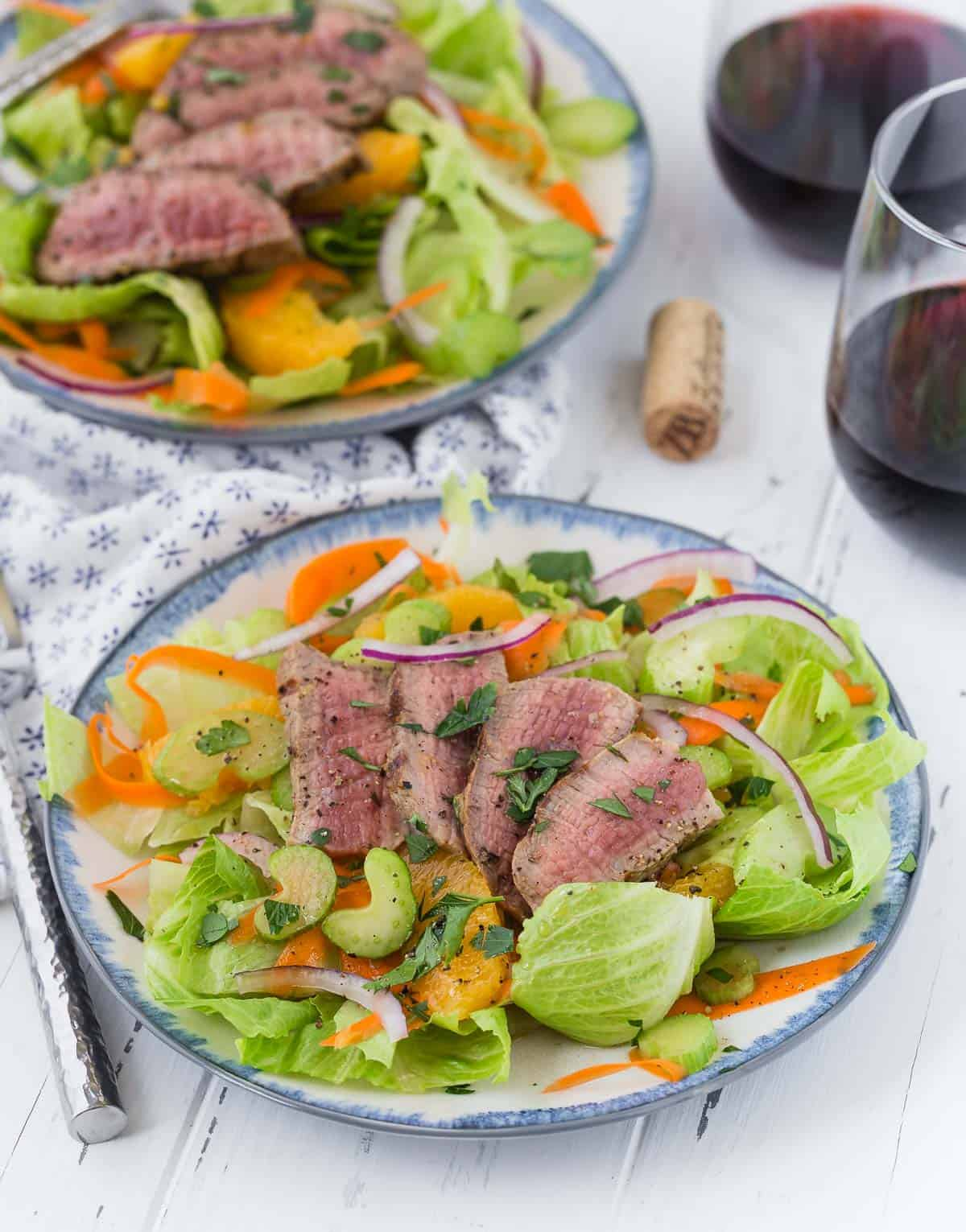 Green leaf lettuce salad topped with steak, oranges, and onion.