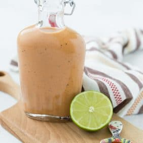 Small glass bottle of sweet bbq salad dressing on a wooden cutting board.