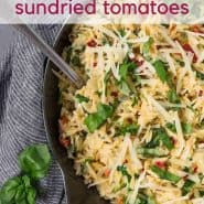 """Overhead image of creamy one pot orzo with spinach, sun-dried tomatoes and fresh basil. Text overlay reads """"one pan orzo with sundried tomatoes"""""""