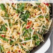 "Overhead image of creamy one pot orzo with spinach, sun-dried tomatoes and fresh basil. Text overlay reads ""one pan orzo with sundried tomatoes"""