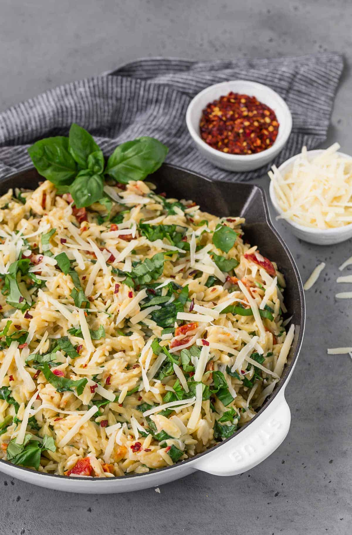 A white and black skillet on a grey surface, filled with creamy orzo with spinach, sundried tomatoes, and basil.