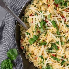 Overhead view of vegetarian orzo in a cast iron skillet, topped with fresh basil and parmesan cheese.
