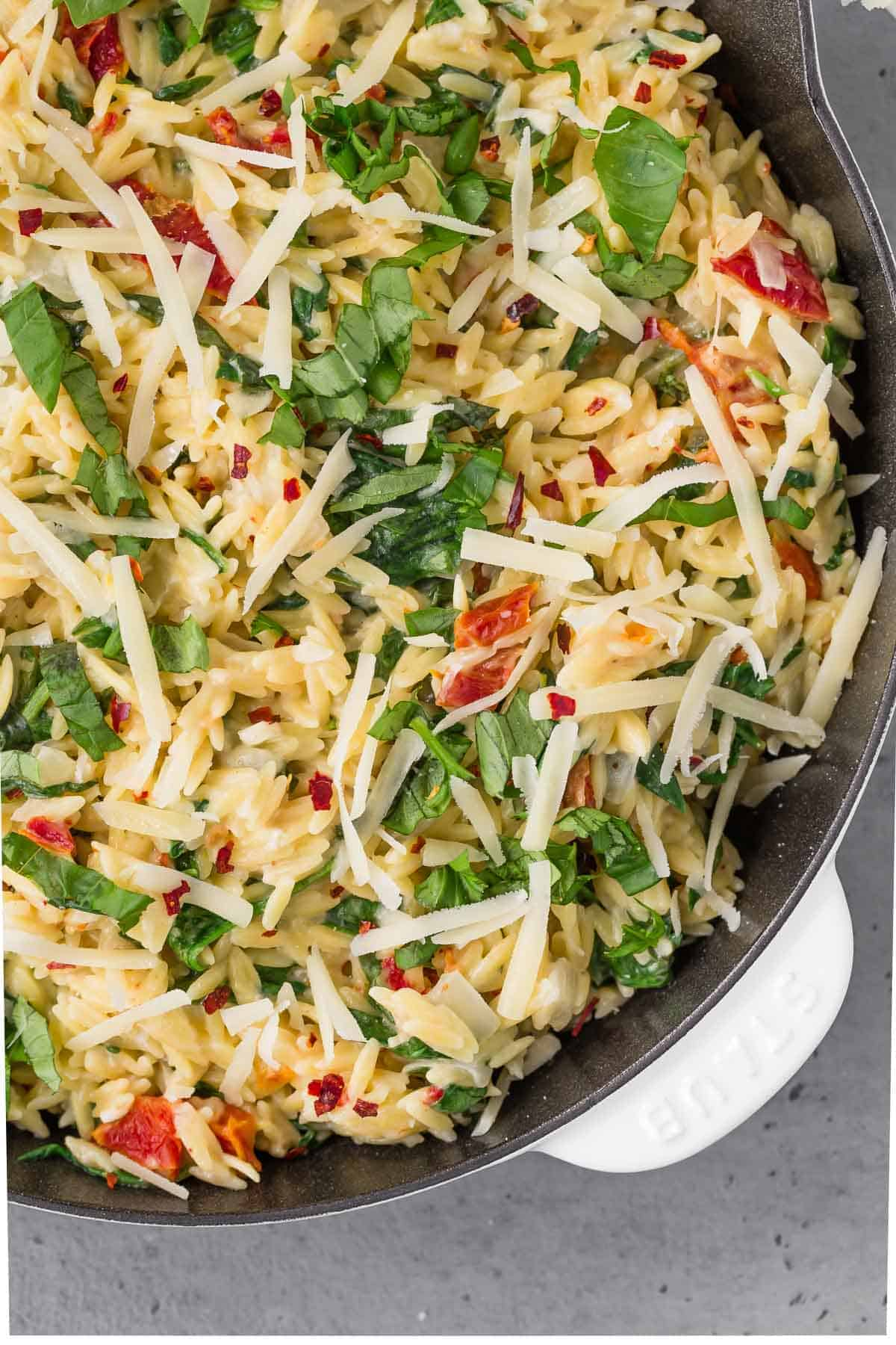 Close up overhead view of creamy orzo in a skillet with sundried tomatoes, basil, parmesan, and red pepper flakes.