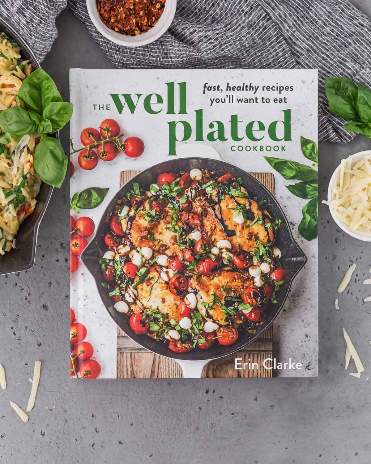 The Well Plated Cookbook on a gray surface. Also pictured are a pasta dish, a small bowl of shredded parmesan cheese, a small bowl of red pepper flakes, and fresh basil.