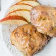 Apple fritters with glaze on a plate with sliced apples.
