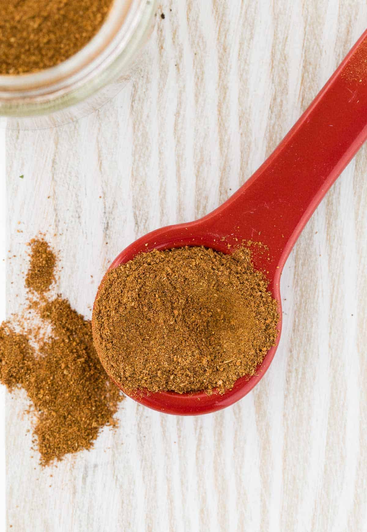 Close up of spices on a red measuring spoon.