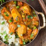 Close up of chicken served with rice, carrots, and a creamy tomato sauce. It is served in a small bowl with rice and cilantro.