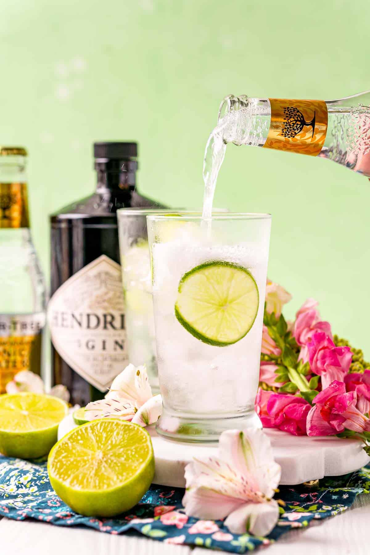Tonic water being poured into a glass with ice and lime.