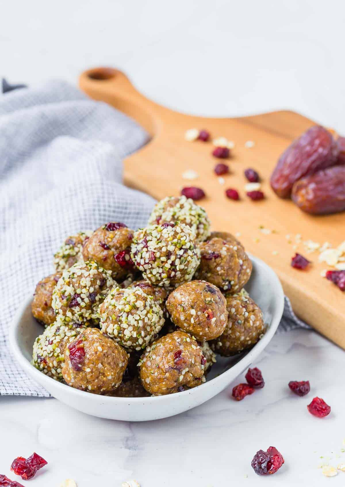 A bowl of energy bites with dried cranberries, dates, and oats in the background.