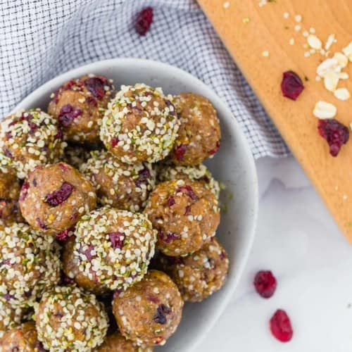 Overhead view of bowl of energy bites, with dried cranberries, oats and hemp seeds also pictured.