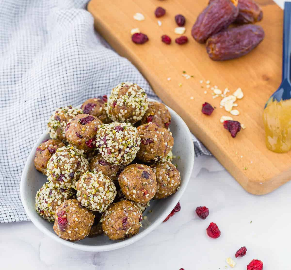 Energy balls in a bowl, in the background dates, oats, sunflower seed butter and dried cranberries are pictured.