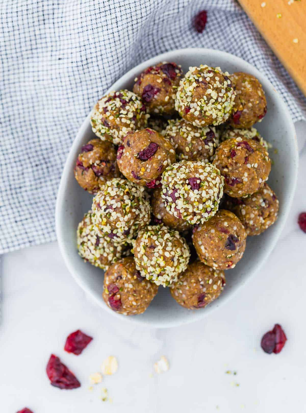Overhead view of oatmeal energy bites in a bowl, with dried cranberries.