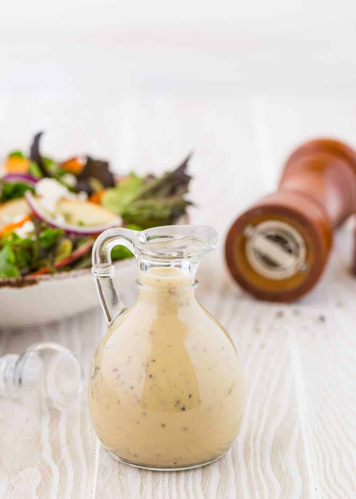 Creamy maple black pepper dressing in a small glass jar with a pour spout and handle.