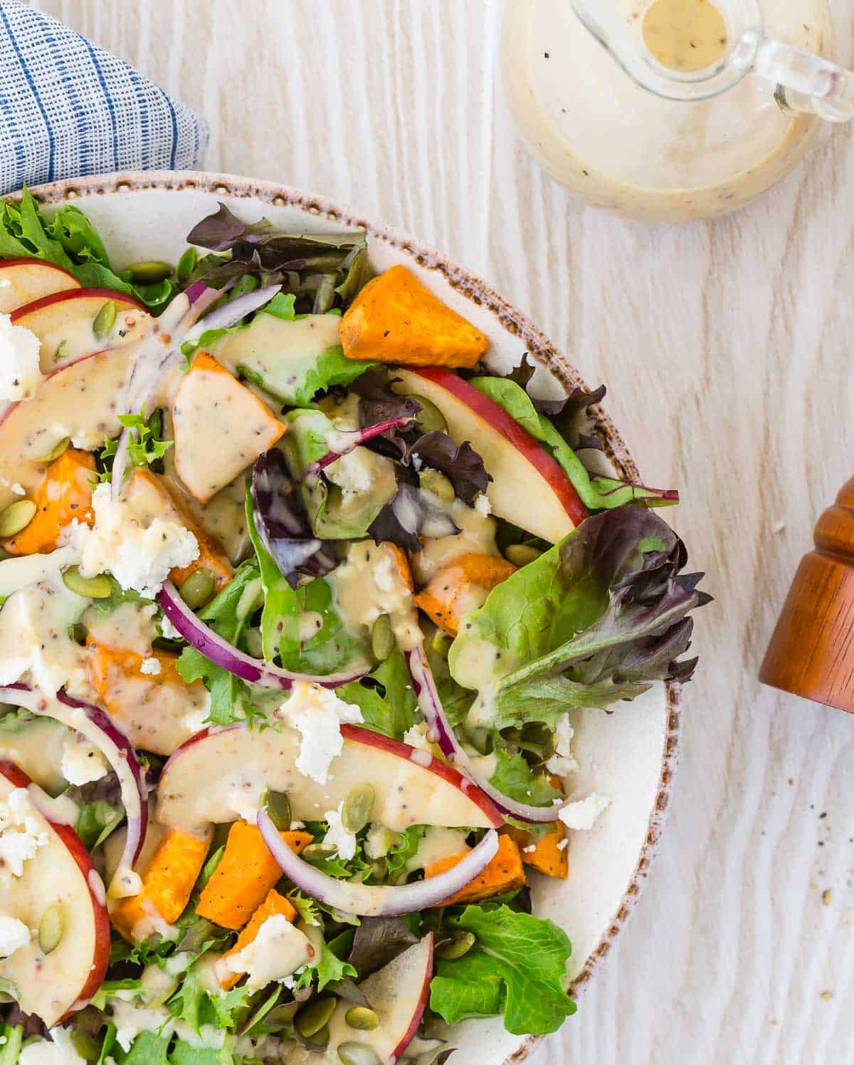 Colorful fall harvest salad with a creamy dressing on a light wood background.