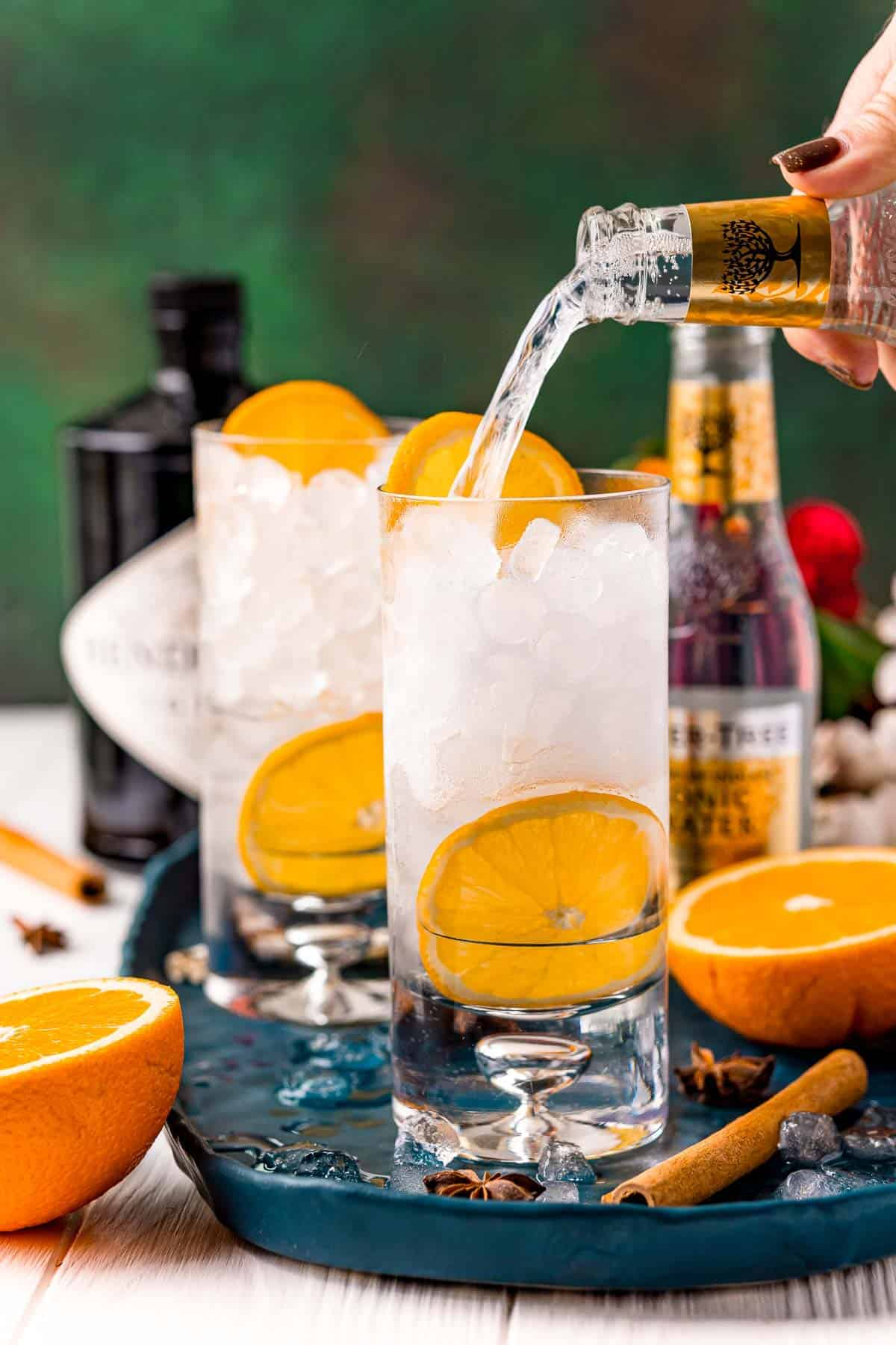 Tonic being poured into a glass with ice and orange slices.