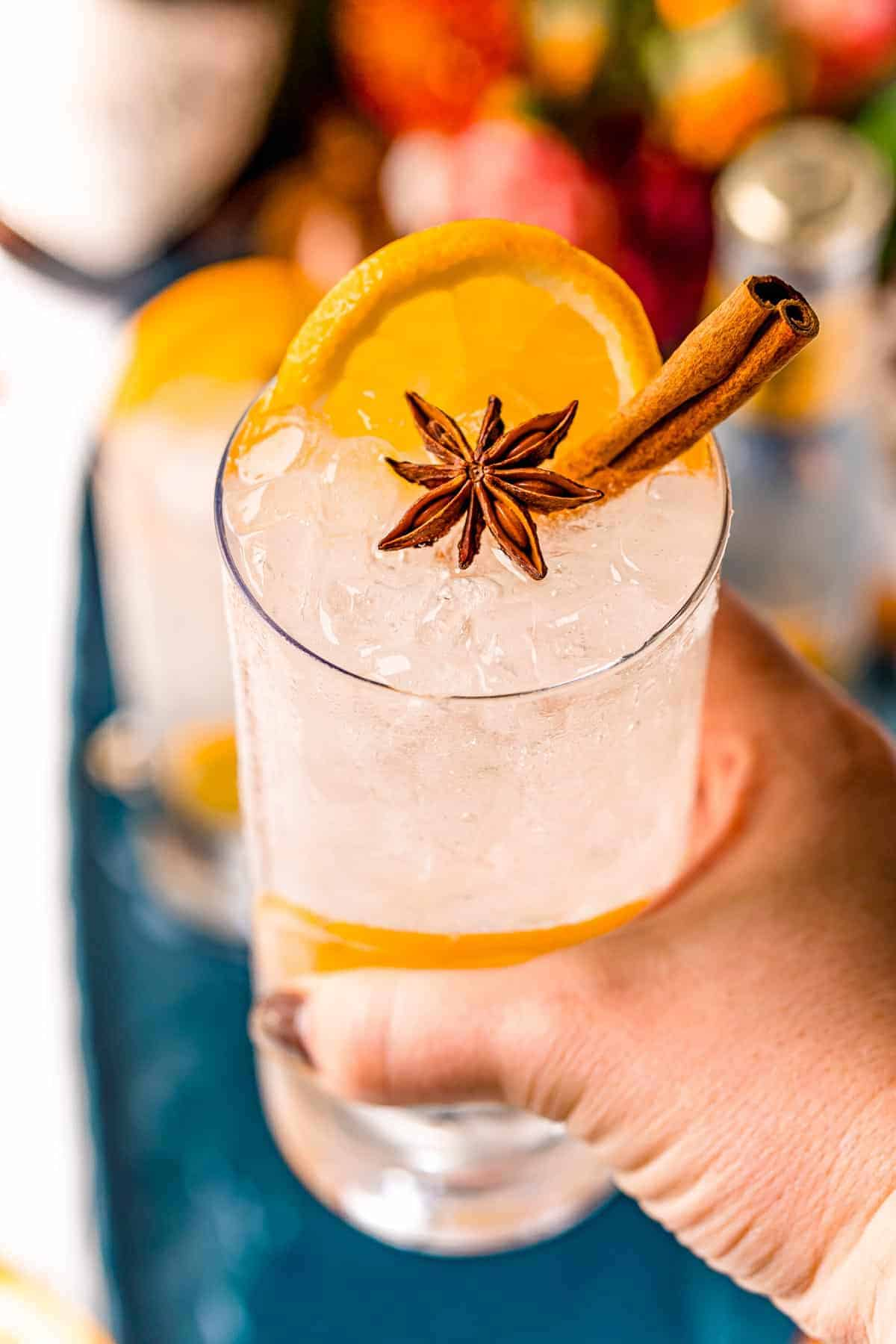 Cocktail with orange and star anise in a hand with painted nails.