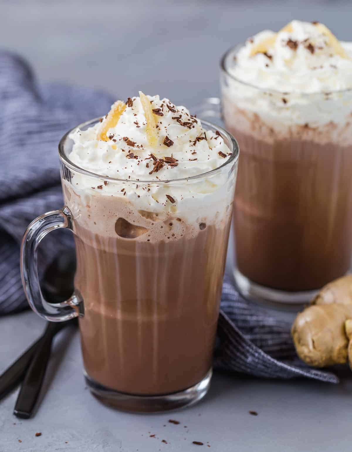 Two mugs of microwave hot chocolate topped with whipped cream, chocolate shavings, and candied ginger.