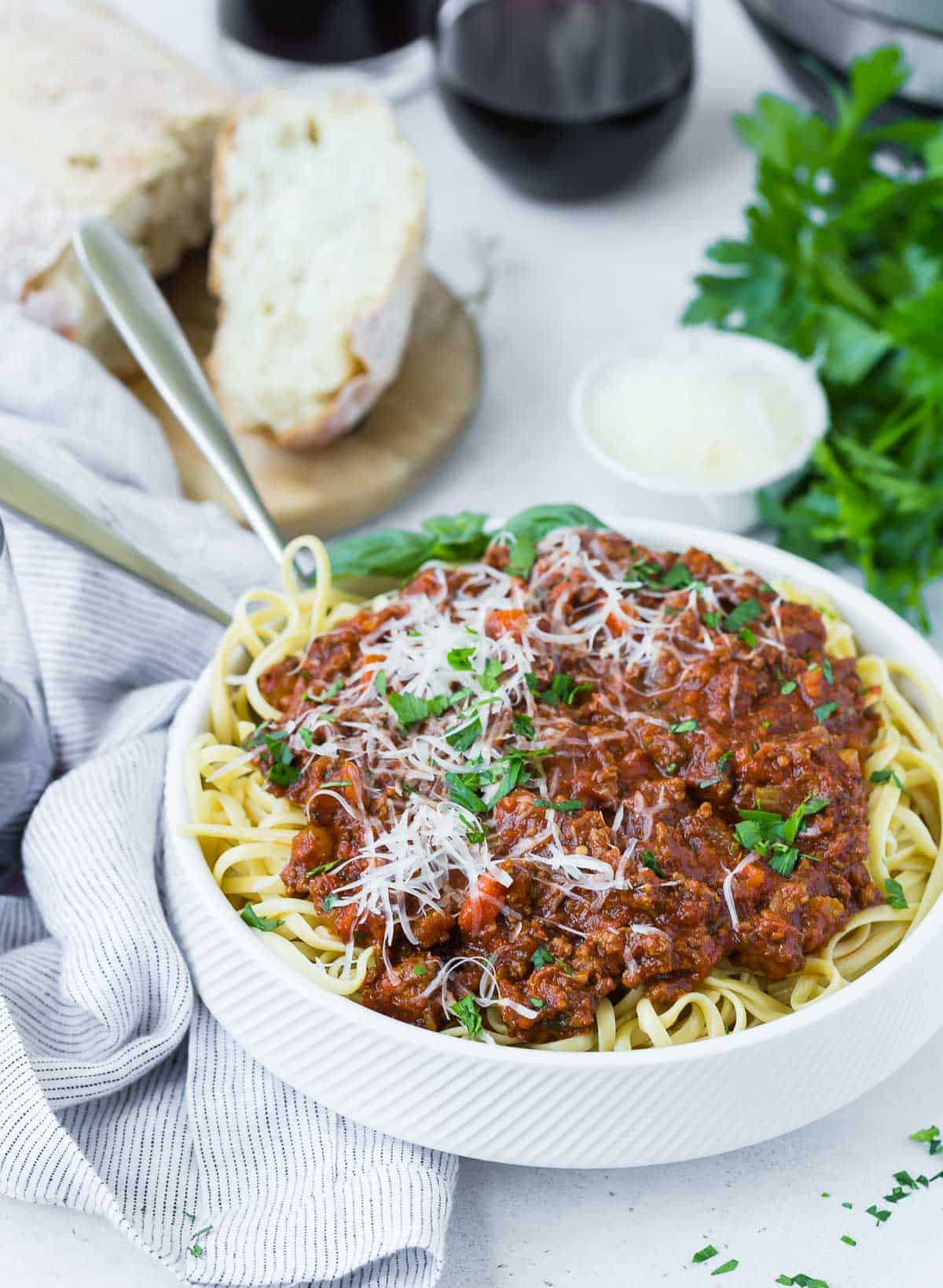 Spaghetti and meat sauce in a white bowl, with wine and bread in the background.