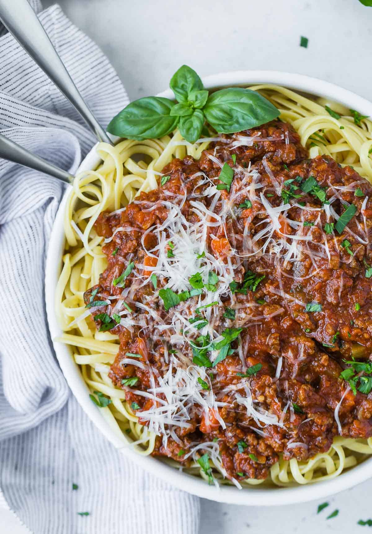 Overhead view of spaghetti and instant pot bolognese sauce in a white bowl, garnished with cheese and fresh basil.