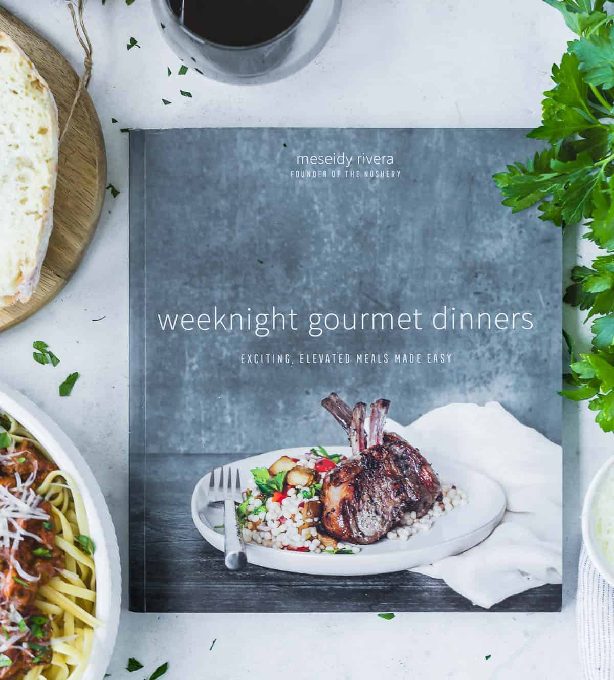 Weeknight Gourmet Dinners cookbook, surrounded by pasta, bread, and fresh herbs.