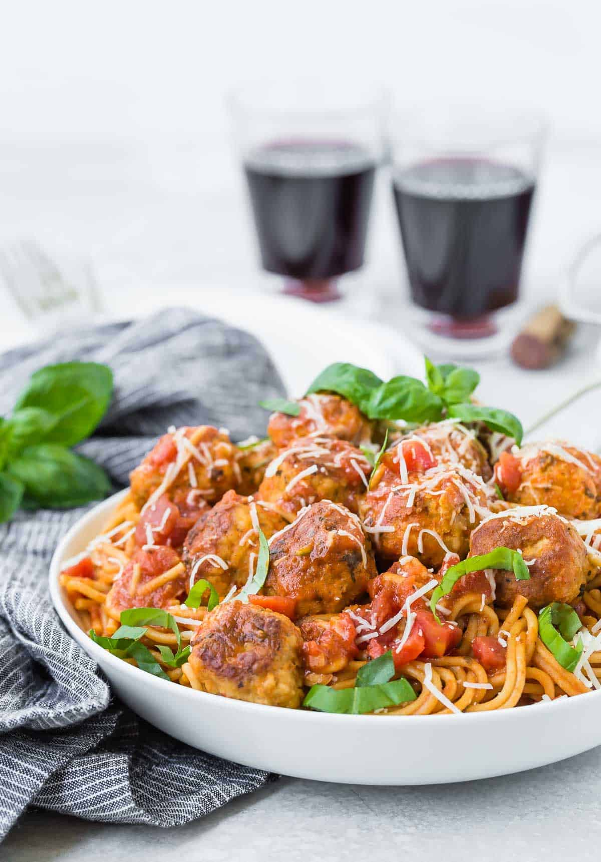 Spaghetti with meatballs, piled high in a white bowl.