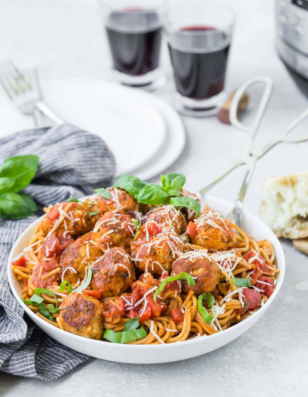 Spaghetti and meatballs with two glasses of wine in the backgorund.