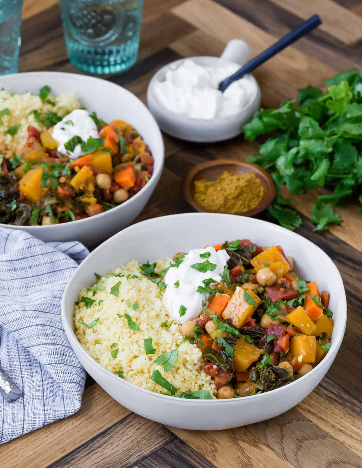 Two bowls of hearty vegetarian stew served over couscous and garnished with greek yogurt.