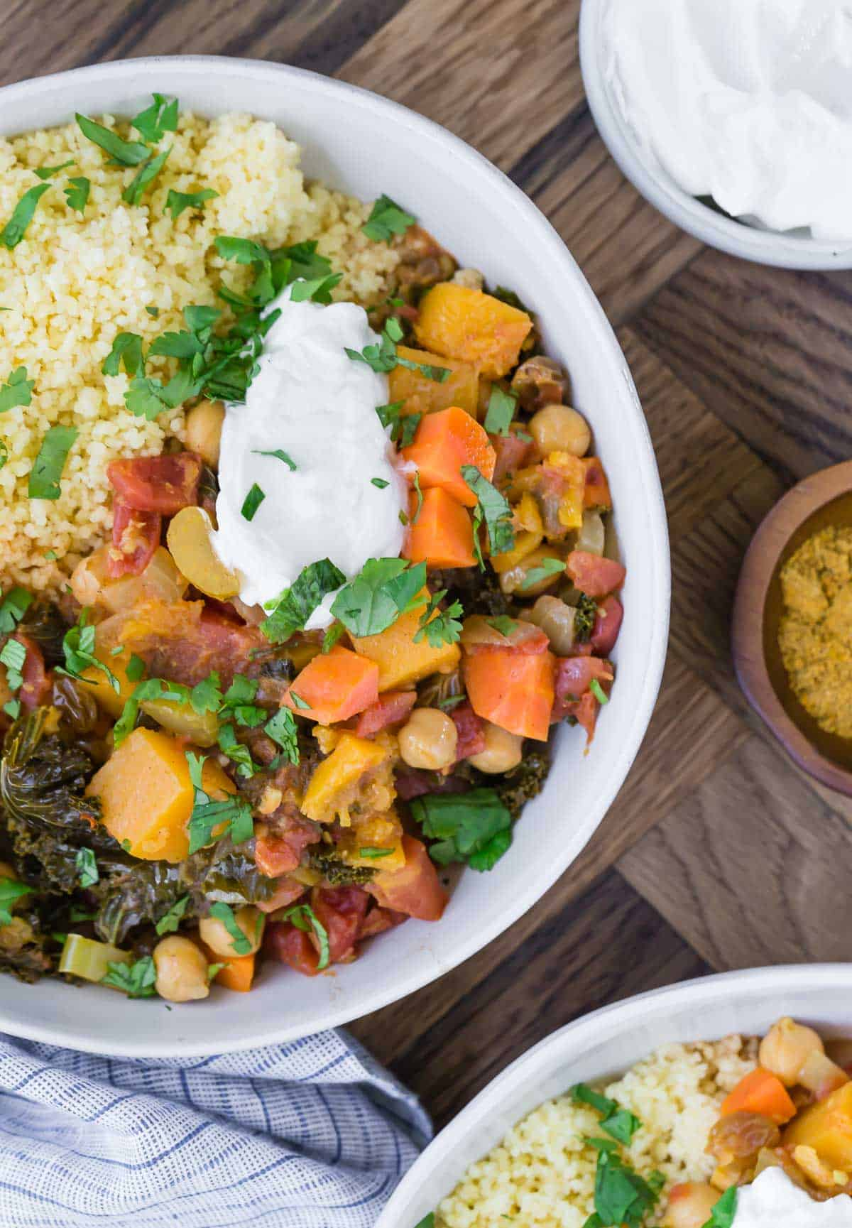 Overhead view of moroccan stew with butternut squash and chickpeas in a white bowl. It is served with yogurt and couscous.